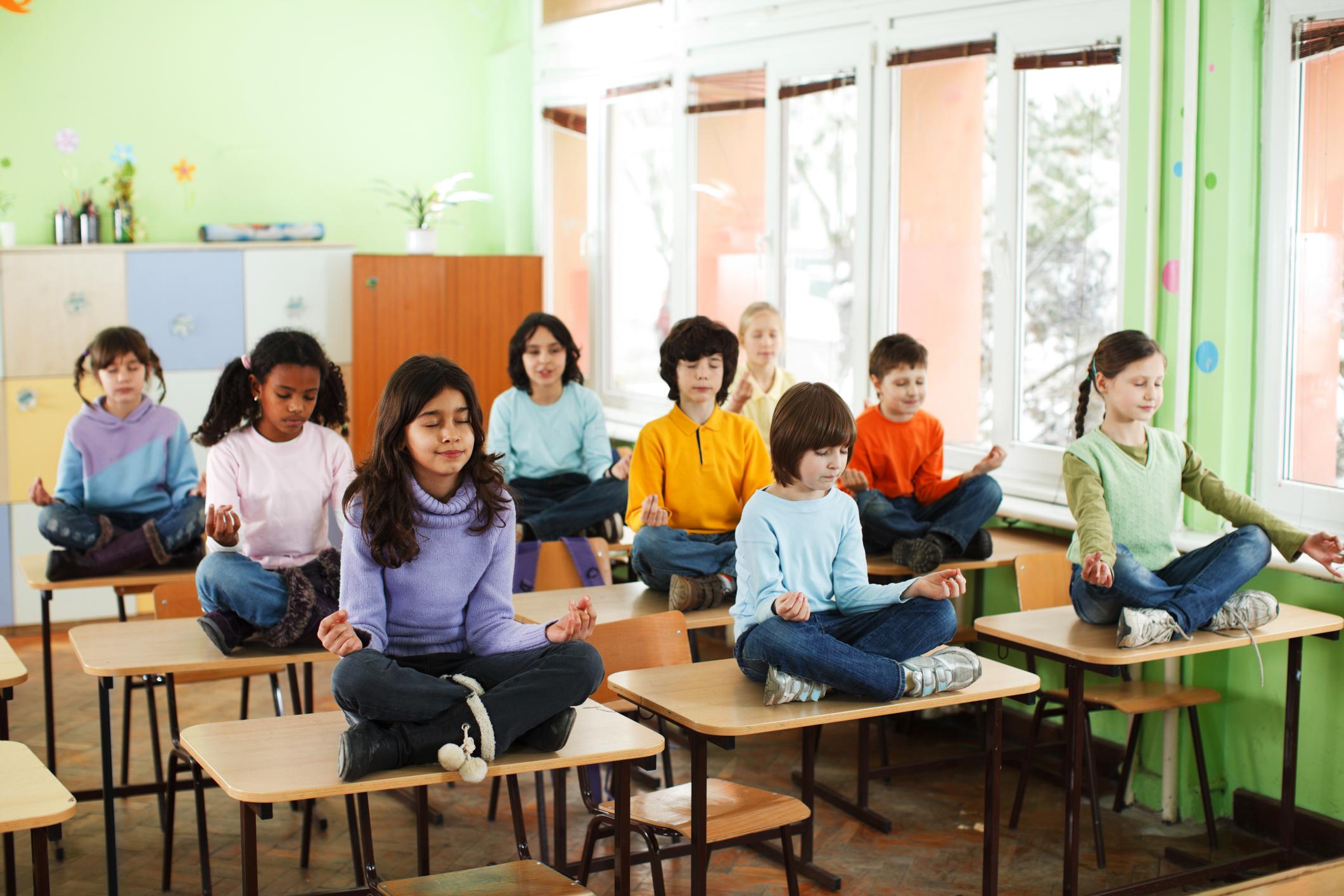 Grupo de alunos pratica meditação em sala de aula. Foto: Getty Images.