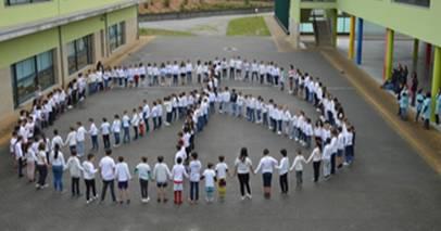 Crianças se reúnem no pátio da escola para formar o símbolo da paz. A atividade foi uma sugestão do projeto 200 Escolas pela Paz e Não-Violência. Foto: Divulgação.