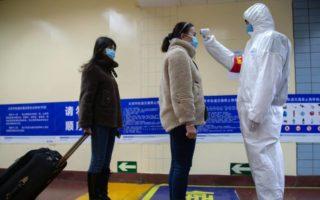 Funcionário mede a temperatura dos passageiros do metrô em Pequim, na China. Foto: Betsy Joles/Getty Images